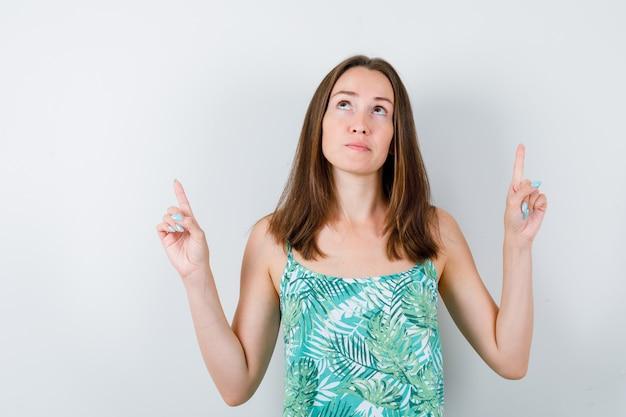 Portret van een jonge dame die in blouse omhoog wijst en zelfverzekerd vooraanzicht kijkt