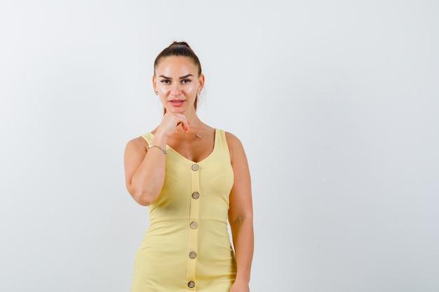 Portret van een jonge dame die kin op hand in gele jurk steunt en op zoek verstandig vooraanzicht