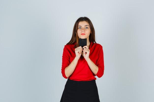 Portret van een jonge dame die mobiele telefoon onder de kin in rode blouse houdt