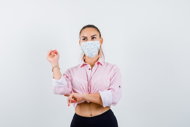 Portret van een jonge dame die naar achteren wijst terwijl ze wegkijkt in shirt, masker en peinzend vooraanzicht kijkt