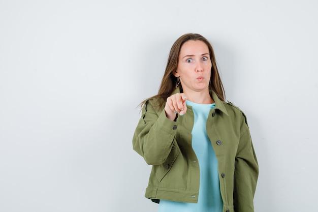 Portret van een jonge dame die naar de camera in t-shirt, jas wijst en een verbaasd vooraanzicht kijkt