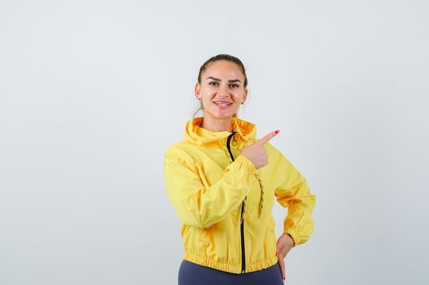 Portret van een jonge dame die naar de rechterbovenhoek in trainingspak wijst en blij vooraanzicht kijkt