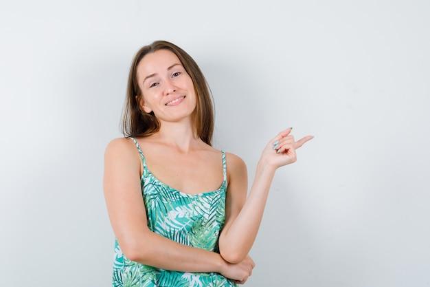 Portret van een jonge dame die naar de rechterkant in blouse wijst en er vrolijk vooraanzicht uitziet
