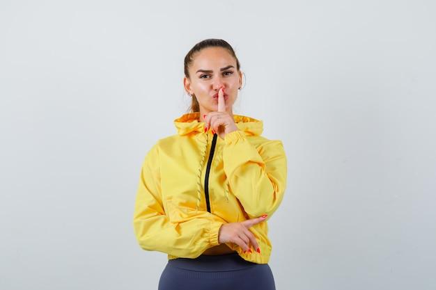 Portret van een jonge dame die naar de rechterkant wijst, een stiltegebaar toont in een gele jas en er zelfverzekerd uitziet
