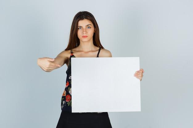 Portret van een jonge dame die naar een leeg canvas in blouse, rok wijst en er serieus vooraanzicht uitziet