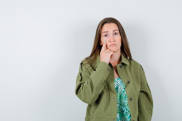 Portret van een jonge dame die naar haar ooglid in een groene jas wijst en teleurgesteld vooraanzicht kijkt
