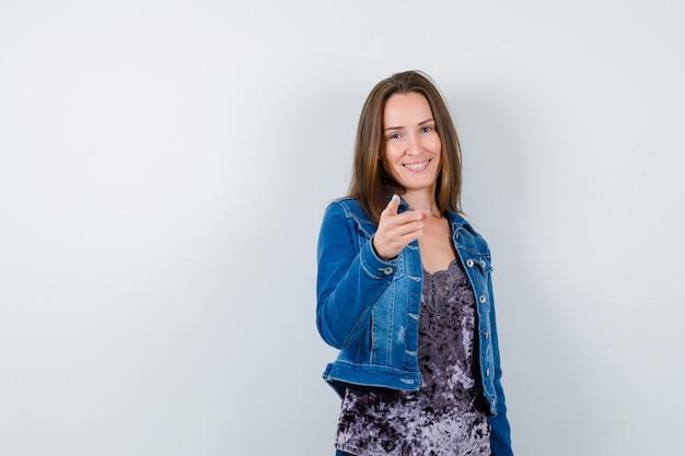 Portret van een jonge dame die naar voren wijst in blouse, spijkerjasje en er vrolijk vooraanzicht uitziet