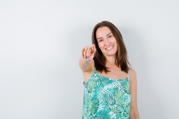 Portret van een jonge dame die naar voren wijst in een blouse en er gelukkig vooraanzicht uitziet