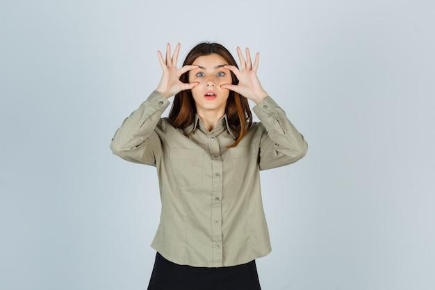 Portret van een jonge dame die ogen opent met vingers in shirt, rok en geschokt vooraanzicht kijkt
