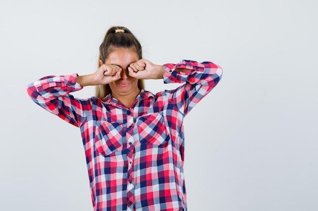 Portret van een jonge dame die ogen wrijft terwijl huilen in geruit overhemd en beledigd vooraanzicht kijkt