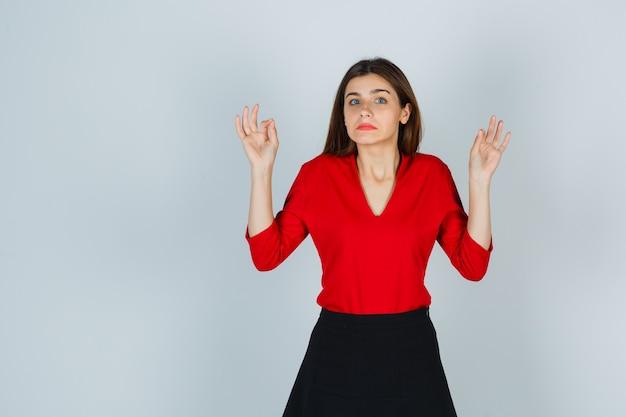 Portret van een jonge dame die ok gebaar in rode blouse, rok toont en aarzelend kijkt
