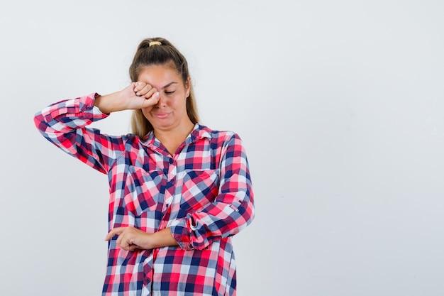 Portret van een jonge dame die oog wrijft terwijl huilen in geruit overhemd en beledigd vooraanzicht kijkt