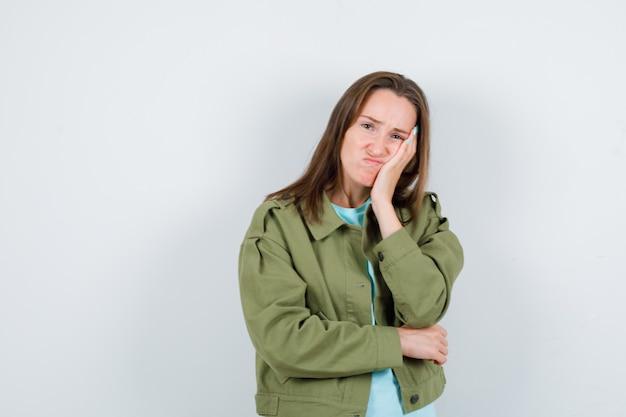 Portret van een jonge dame die op haar wang leunt in t-shirt, jas en er somber vooraanzicht uitziet