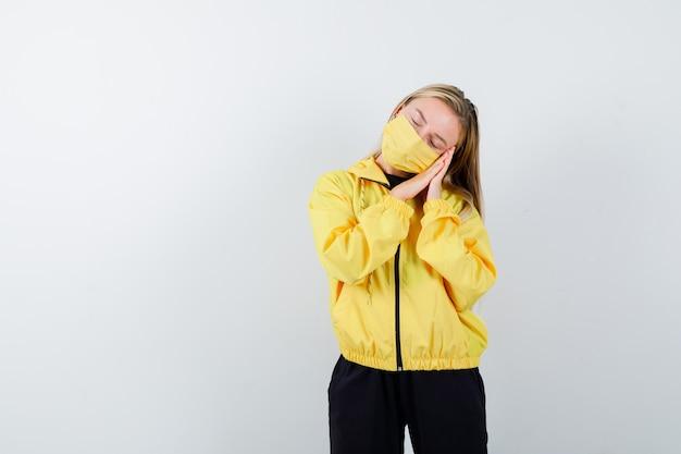 Portret van een jonge dame die op handpalmen leunt als hoofdkussen in trainingspak, masker en slaperig vooraanzicht kijkt