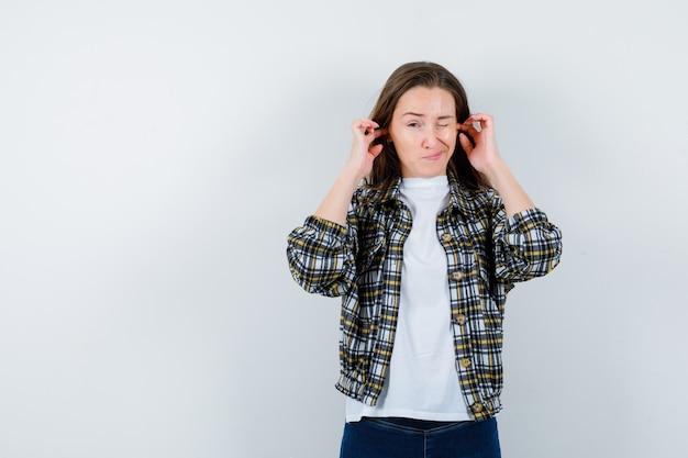 Portret van een jonge dame die oren met vingers in t-shirt, jasje inplugt en aarzelend vooraanzicht kijkt