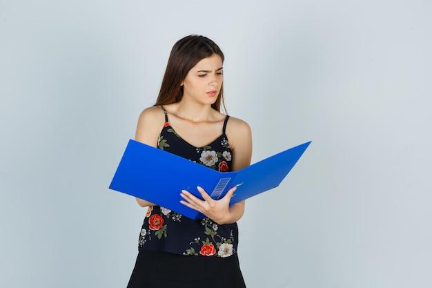 Portret van een jonge dame die over map in blouse kijkt en verward vooraanzicht kijkt