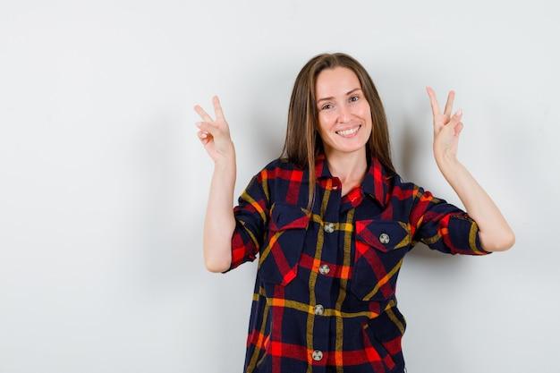 Portret van een jonge dame die overwinningsgebaar in casual overhemd toont en zelfverzekerd vooraanzicht kijkt