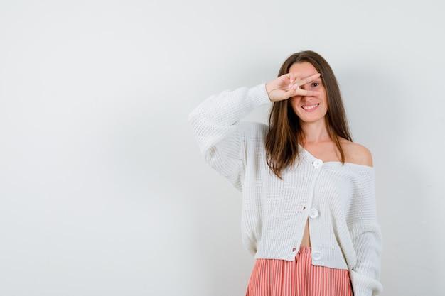 Portret van een jonge dame die overwinningsteken in vest en rok toont die geïsoleerd gelukkig kijken
