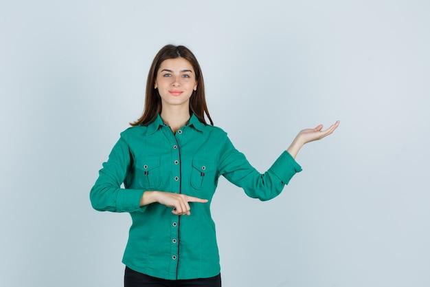 Portret van een jonge dame die verwelkomend gebaar toont terwijl ze opzij wijst in een groen shirt en op zoek is naar vrolijk vooraanzicht