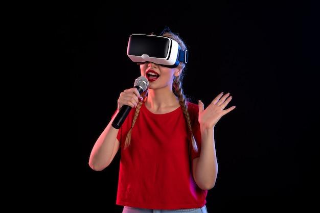 Portret van een jonge dame die vr speelt en zingt op donkere, ultrageluid visuele muziek