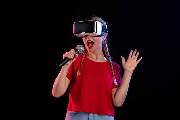 Portret van een jonge dame die vr speelt en zingt op een visueel spel met donkere muziek