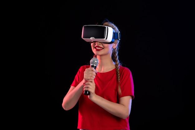 Portret van een jonge dame die vr speelt en zingt op het visuele echografie-spel met donkere muziek