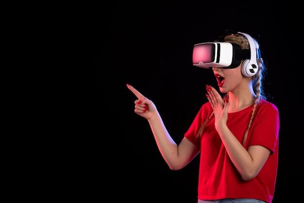 Portret van een jonge dame die vr speelt in een koptelefoon op een donkere vloer visuele echografie