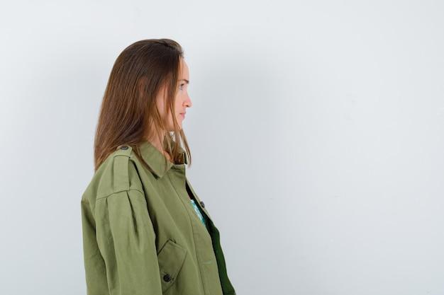Portret van een jonge dame die wegkijkt, zijwaarts staat in een groene jas en er gefocust uitziet