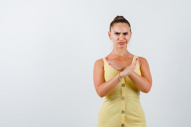 Portret van een jonge dame die weigeringsgebaar in gele jurk toont en ontevreden vooraanzicht kijkt
