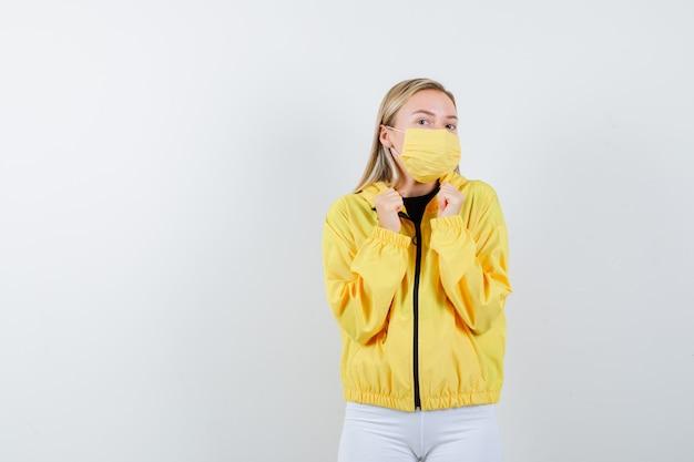 Portret van een jonge dame die winnaargebaar in jasje, broek, masker toont en gelukkig vooraanzicht kijkt