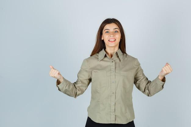 Portret van een jonge dame die winnaargebaar in overhemd, rok toont en gelukkig vooraanzicht kijkt