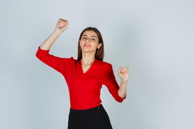 Portret van een jonge dame die winnaargebaar in rode blouse toont