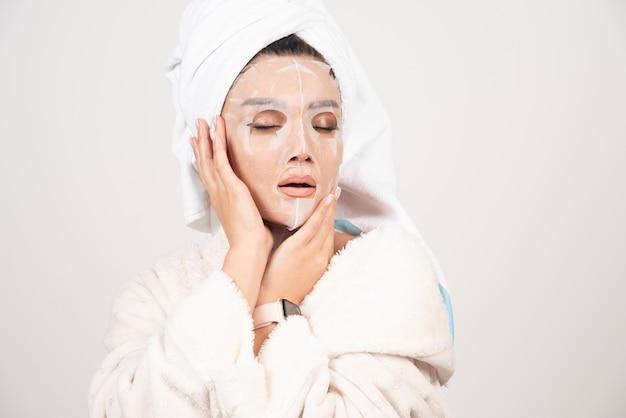 Portret van een jonge dame in badjas en handdoek op het hoofd terwijl ze haar gezicht met gezichtsmasker aanraakt.