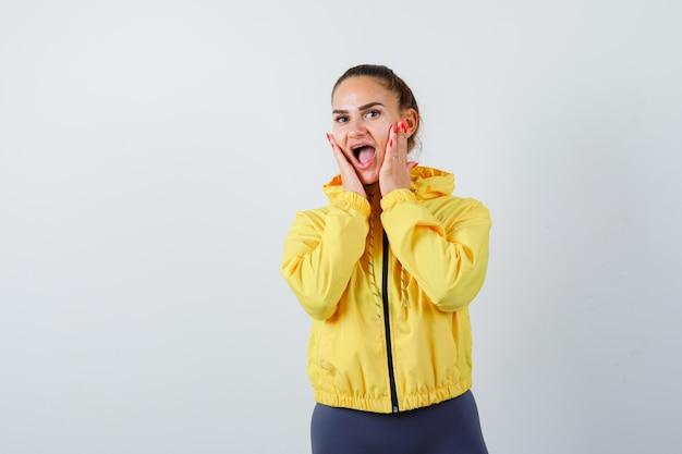 Portret van een jonge dame met de handen op de wangen terwijl ze de mond in een gele jas opent en een verbaasd vooraanzicht kijkt