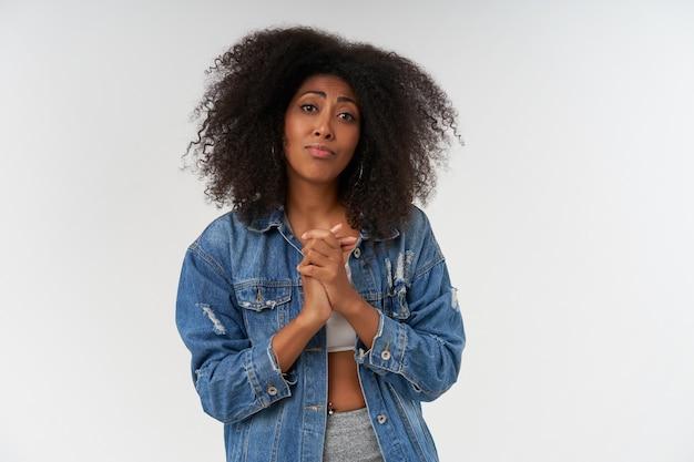 Portret van een jonge dame met een donkere huidskleur met krullend haar dat gevouwen handen opheft en klagend, lippen tuit en voorhoofd rimpelt terwijl ze over een witte muur poseert