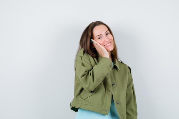 Portret van een jonge dame met hand op wang in t-shirt, jas en ziet er prachtig uit vooraanzicht