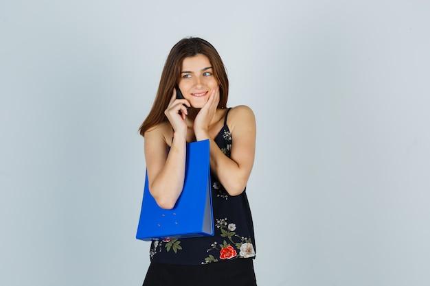 Portret van een jonge dame met map, pratend op mobiele telefoon, hand op wang in blouse en opgewonden vooraanzicht