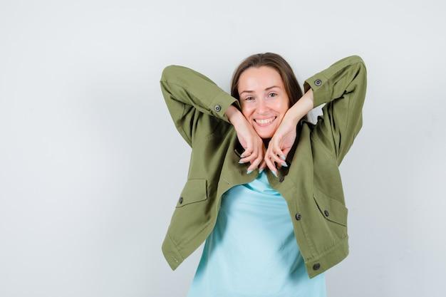 Portret van een jonge dame met polsen op de wangen in een t-shirt, jas en een schattig vooraanzicht