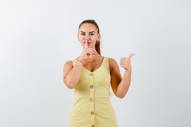 Portret van een jonge dame met stilte gebaar, opzij wijzend met duim in gele jurk en op zoek naar verstandig vooraanzicht