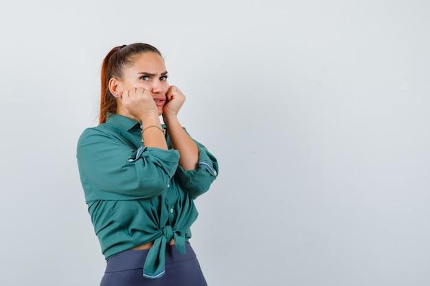 Portret van een jonge dame met vuisten op de wangen, zijwaarts in shirt, broek en teleurgesteld.
