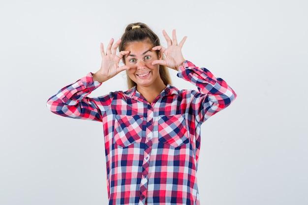Portret van een jonge dame ogen openen met vingers in geruit overhemd en vrolijk vooraanzicht kijken