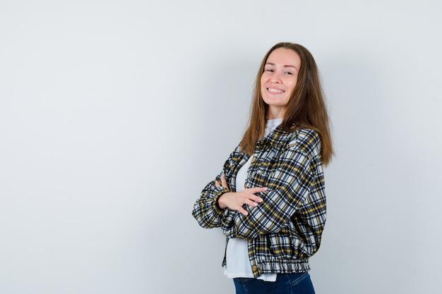 Portret van een jonge dame permanent met gekruiste armen in t-shirt, jasje en op zoek naar zelfverzekerd vooraanzicht