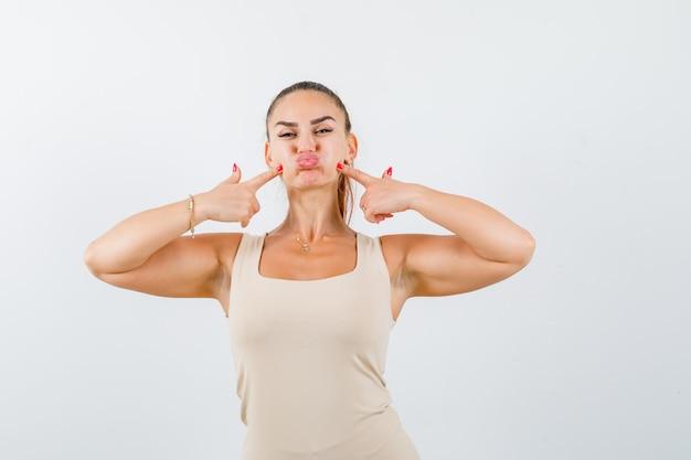 Portret van een jonge dame vingers op gezwollen wangen in mouwloos onderhemd te drukken en op zoek grappig vooraanzicht