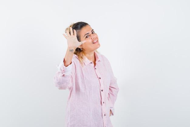 Portret van een jonge dame zwaaiende hand om afscheid te nemen in roze shirt en op zoek blij vooraanzicht