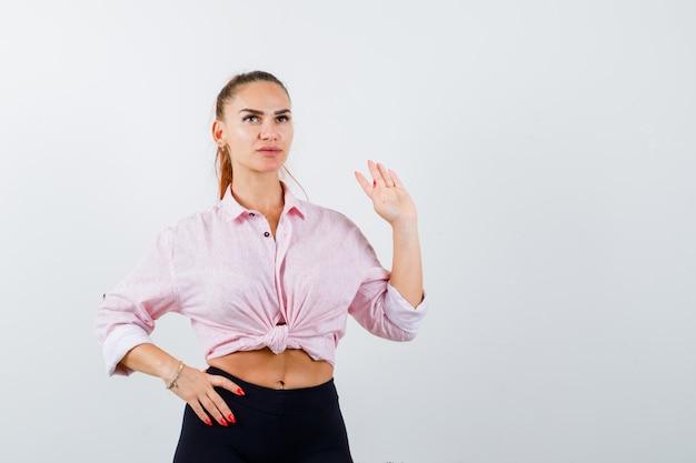 Portret van een jonge dame zwaaiende hand om afscheid te nemen in shirt, broek en op zoek naar zelfverzekerd vooraanzicht
