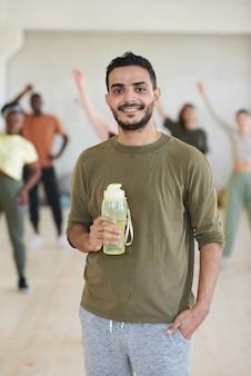 Portret van een jonge danseres glimlachend in de camera en drinkwater na sportopleiding