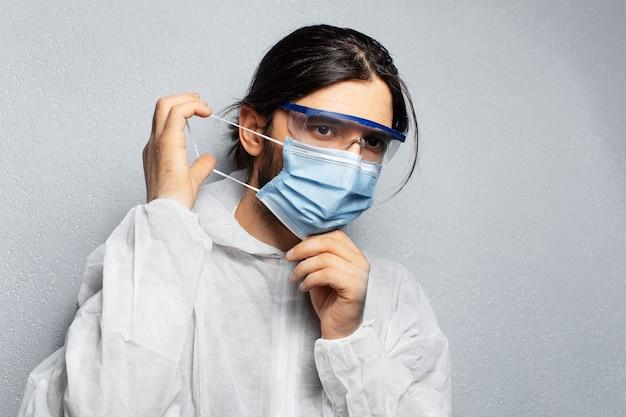 Portret van een jonge dokter in het dragen van een pbm-pak, het opzetten van een medisch gezichtsmasker tegen coronavirus, covid-19. achtergrond van grijze muur.