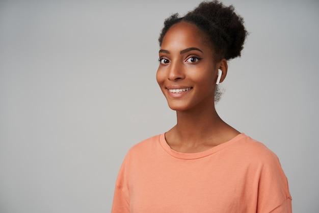 Portret van een jonge donkerbruine vrouw met bruine ogen en een broodje kapsel op zoek vrolijk met een brede glimlach, geïsoleerd op grijs