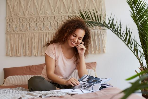 Portret van een jonge donkere dame met krullend haar, zit op het bed en raakt de wang, glimlacht en leest een nieuw tijdschrift, geniet thuis van vrije tijd.