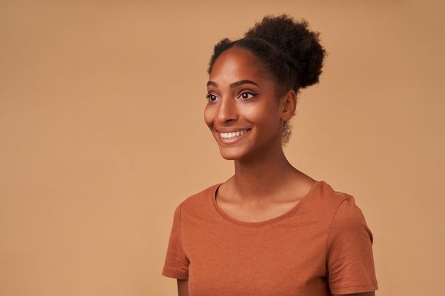 Portret van een jonge donkere gekrulde vrouw die positief opzij kijkt met een charmante glimlach terwijl ze op beige in bronzen t-shirt staat